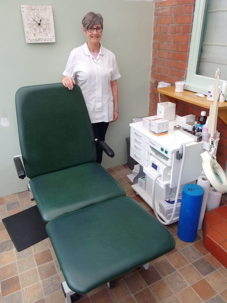Woman standing next to Chiropodists Couch with equipment to the side